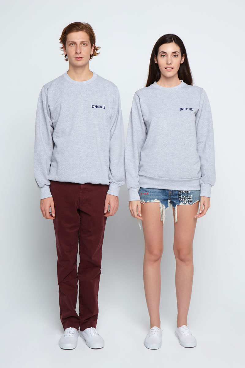 Couple wearing the same grey sweatshirts standing
